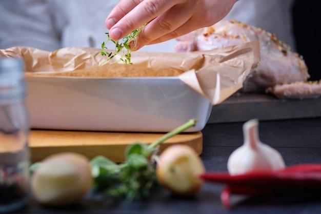 Der mensch fügt thymian zu neuen kartoffeln hinzu. der prozess des kochens von hühnchen mit gewürzen und zitrone im ofen.