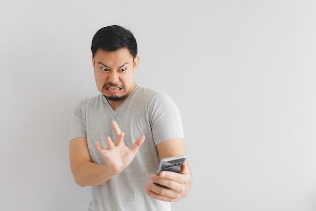 Der mensch fühlt sich hassen und angewidert über die show auf dem smartphone.