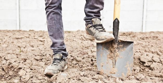Der mensch gräbt auf seinem landhaus boden