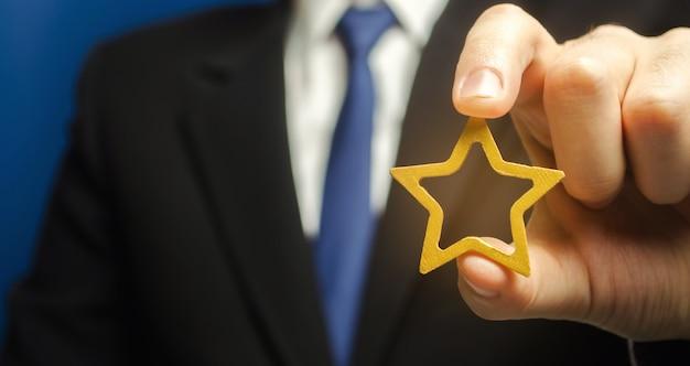 Der mensch hält einen goldenen stern in der hand