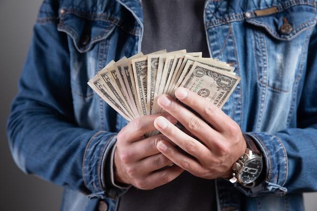 Der mensch hält geldbündel und shows