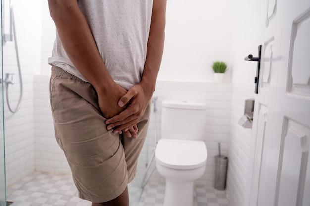 Der mensch hält seine genitalien in der toilette
