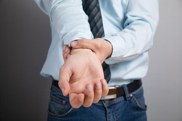 Der mensch hat schmerzen am handgelenk auf der grauen oberfläche