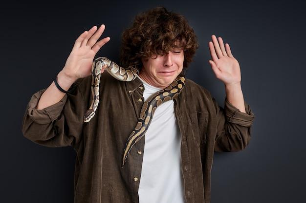 Der mensch kann sich nicht bewegen, wenn sich eine schlange um hals und schultern legt, unter schock steht und weint
