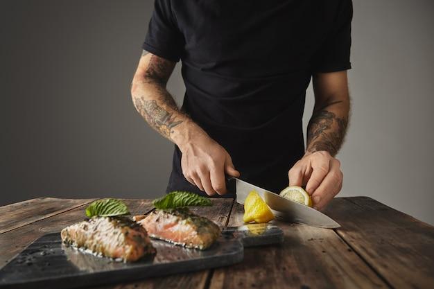 Der mensch kocht eine gesunde mahlzeit, schneidet limon hinter sich, dekoriert mit minzblatt, zwei rohen lachsstücken in weißweinwurst mit gewürzen und kräutern, die auf einem für den grill vorbereiteten marmordeck präsentiert werden