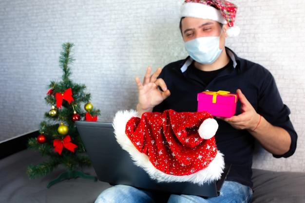 Der mensch kommuniziert über die gebärdensprache. kerl mit weihnachtsmütze in der nähe des laptops interagiert durch videoanrufe. leben mit behinderung. weihnachten in isolation zu hause. soziale distanzierung für feiertage.