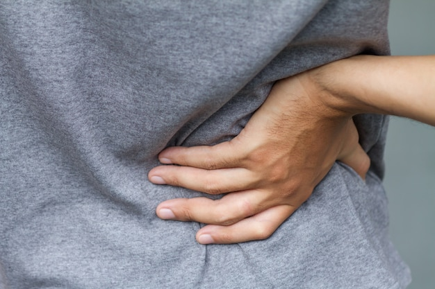 Der mensch leidet unter rückenschmerzen und bandscheibenversetzungen