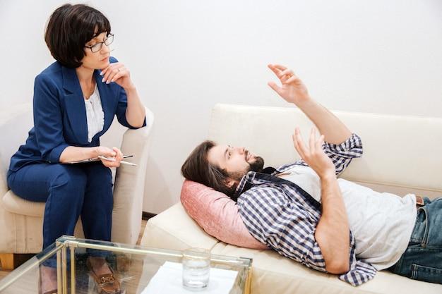Der mensch liegt auf dem sofa und winkt mit den händen. er ist im moment ziemlich emotional.