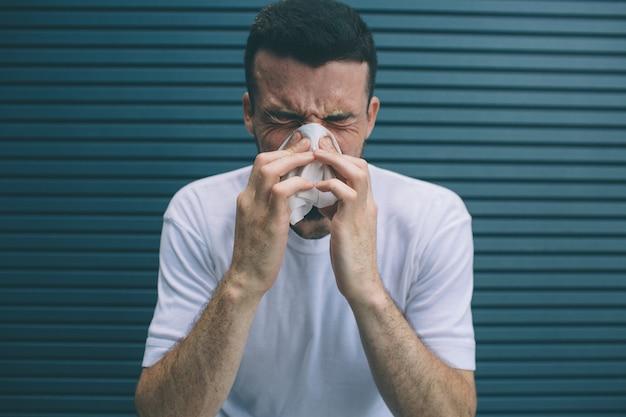 Der mensch niest und bedeckt nase und mund mit einer serviette. er fühlt sich schlecht. isoliert auf gestreift