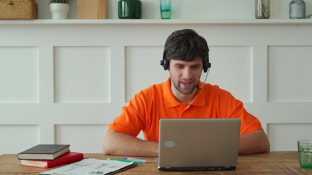 Der mensch nutzt ein headset, um an seinem arbeitsplatz online zu sprechen. der selbstbewusste mann sitzt am schreibtisch und schaut auf den laptop-bildschirm