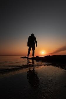 Der mensch schaut auf die morgendämmerung am frühen morgen auf dem fluss