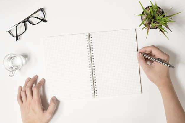 Der mensch schreibt etwas auf sein notizbuch. draufsicht flach liegend.