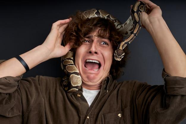 Der mensch schreit emotional, mit der schlange auf dem kopf, er hat angst vor exotischen ungewöhnlichen tieren aus der wilden natur