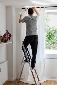Der mensch steht auf einer trittleiter neben dem fenster und hängt weiße vorhänge an die gardinenstange