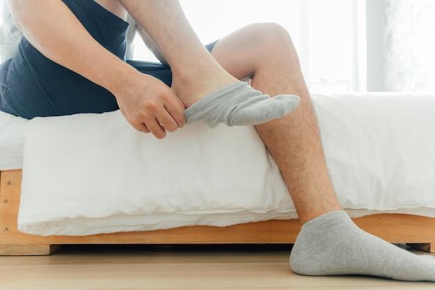 Der mensch trägt im schlafzimmer socken in die füße. konzept, fertig zu werden und sich zu verkleiden.