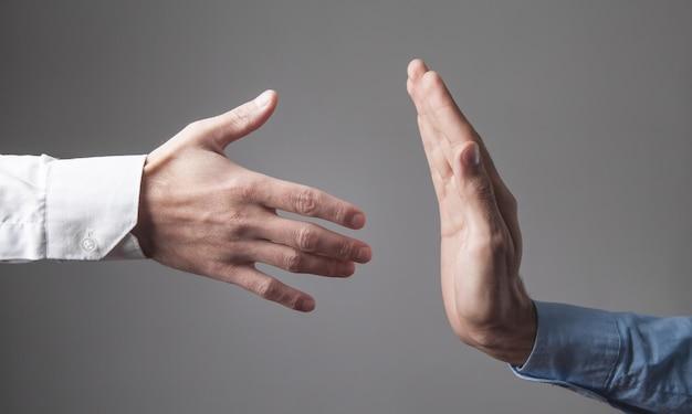 Der mensch weigert sich, dem geschäftsmann die hand zu geben