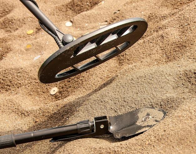 Der metalldetektor, ring und spaten auf dem sand