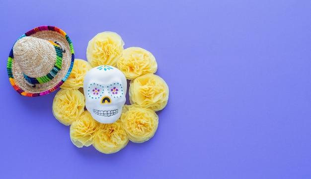 Der mexikanische schädel, der durch gelbes papiercempasuchil umgeben wird, blüht auf veilchen