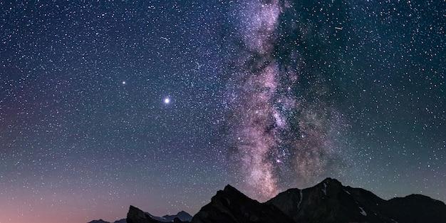 Der milchstraßenkern und leuchtende sterne am nachthimmel über den alpen