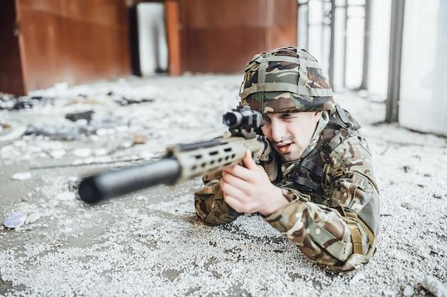 Der militärsoldat in der uniform lag auf dem boden und hält in den händen eines großen gewehrs