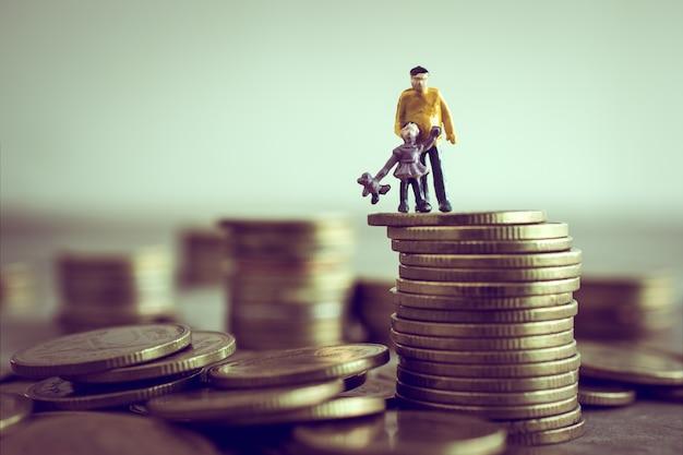Der miniaturvati und kinder, die auf das geld stehen, sparen geldkonzept.