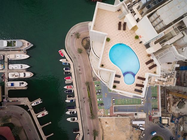 Der mit blauem wasser gefüllte pool steht in der nähe einiger brauner stühle.