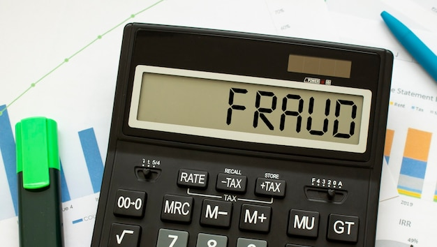 Der mit fraud gekennzeichnete taschenrechner liegt auf finanzdokumenten im büro