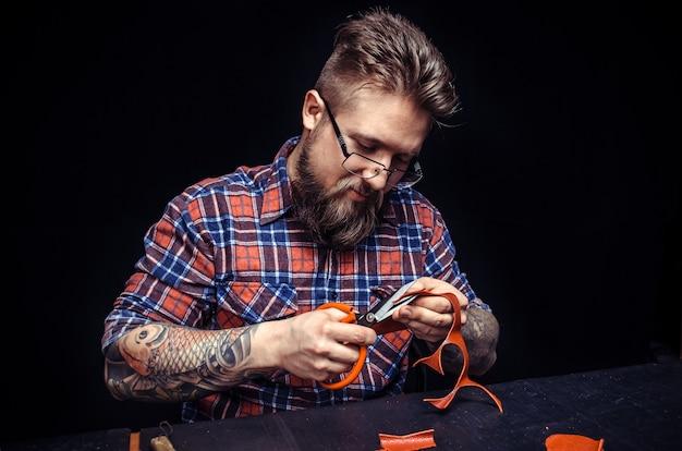 Der mit leder arbeitende handwerker demonstriert in seiner werkstatt den lederschneideprozess