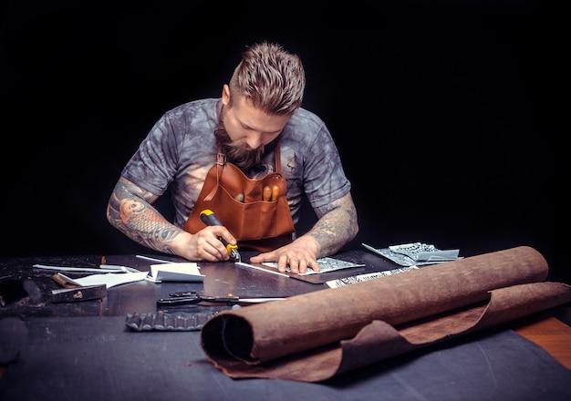 Der mit leder arbeitende handwerker stellt ein neues produkt aus leder her. / der kunsthandwerker schneidet in seinem geschäft lederwaren aus.