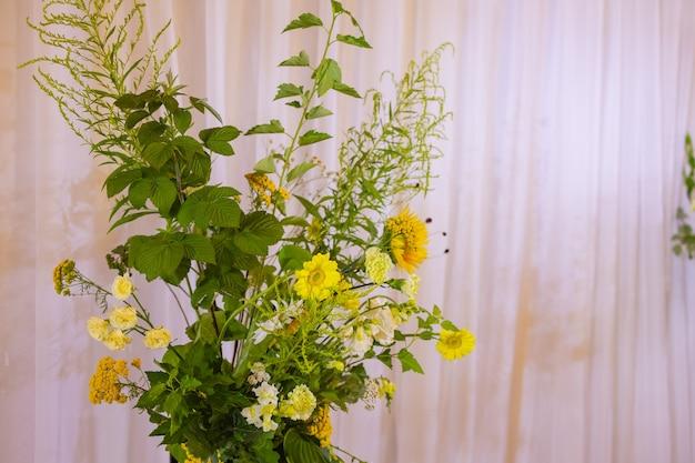 Der mit stoffblumen und grün geschmückte bogen für die hochzeitszeremonie befindet sich in einem kiefernwald.