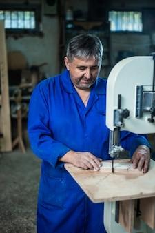 Der mitarbeiter bohrt den gegenstand in der werkstatt mit hilfe einer bohrmaschine