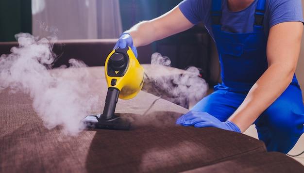 Der mitarbeiter der chemischen reinigung entfernt schmutz von den möbeln in einer flachen nahaufnahme.