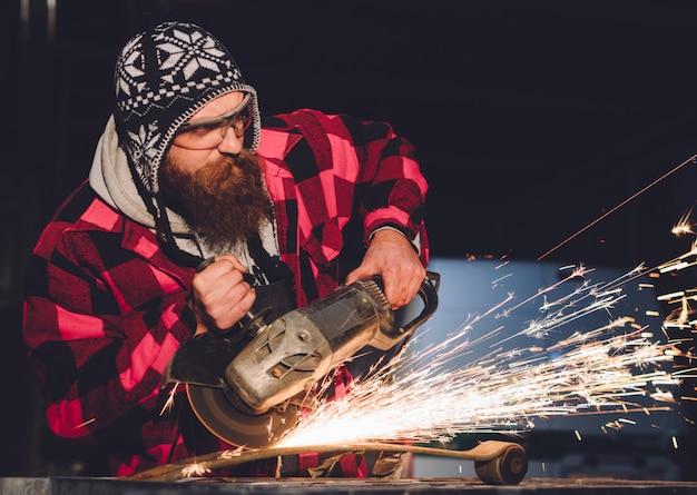 Der mitarbeiter der servicestation fertigt karosseriereparaturen mit einem schweißgerät in handfunken