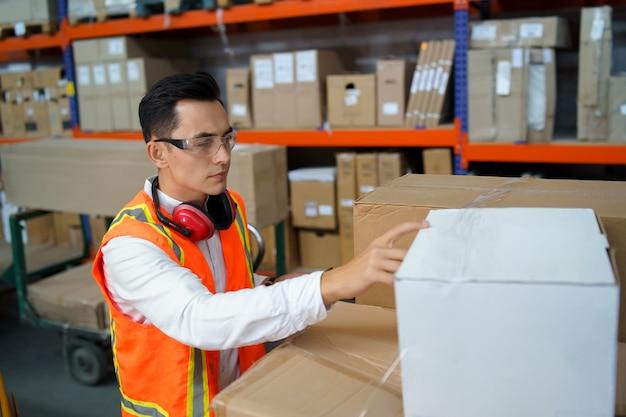 Der mitarbeiter eines logistiklagers führt eine warenbestandsaufnahme durch