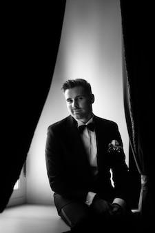 Der modische bräutigam erwartet die braut am fenster. schwarzweiss-porträt des bräutigams in einem schwarzen anzug