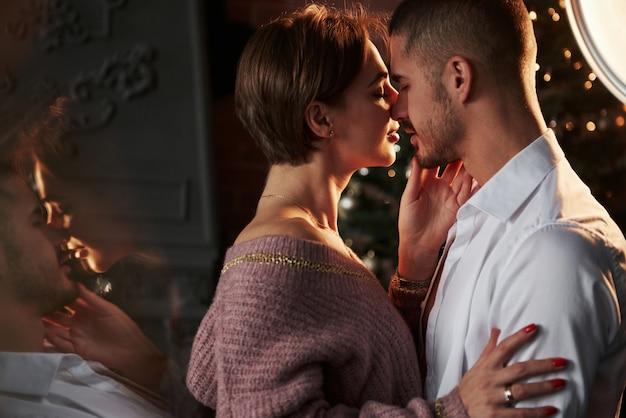 Der moment, auf den sie gewartet hatten. die nähe des mannes und des mädchens in luxuskleidung, die tanzen und flirten. wunderschöne spiegelung von der seite.