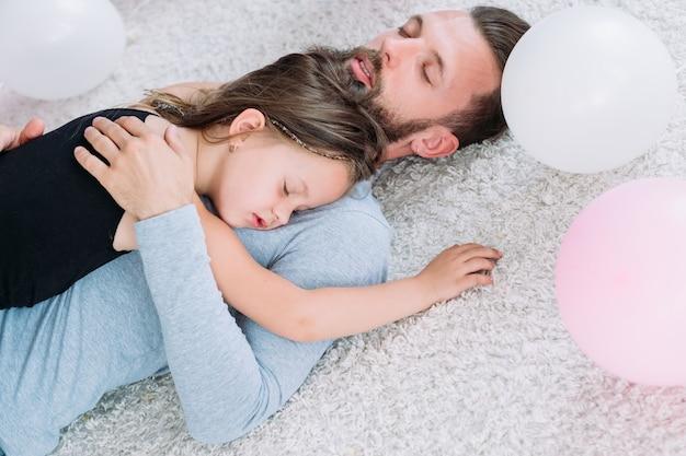 Der müde, erschöpfte vater schlief ein und umarmte seine kleine hyperaktive tochter. vaterschaft und kindheit süße momente der liebe und fürsorge.