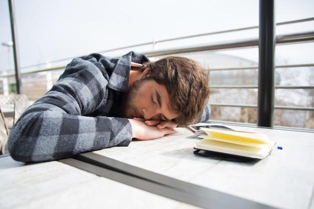 Der müde student, der mit seinem kopf schläft, ruhte auf tabelle aus