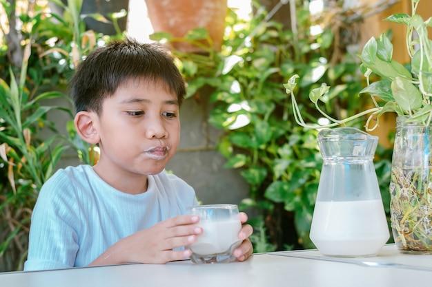 Der mund des jungen war mit milchflecken befleckt, nachdem er die milch aus dem glas getrunken hatte.