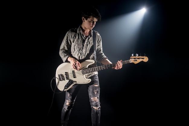 Der musiker spielt bassgitarre auf einem schwarzen hintergrund mit einem lichtstrahl, emotionales spiel, musikkonzept