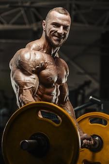 Der muskulöse bodybuildereignungsmann, der arme tut, trainiert in der turnhalle