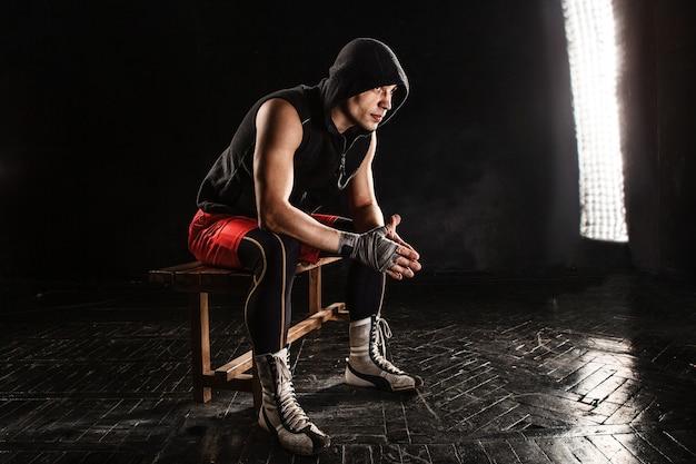 Der muskulöse boxer sitzt und ruht auf schwarz