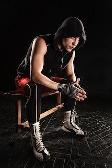 Der muskulöse mann, der auf schwarzem sitzt und stillsteht