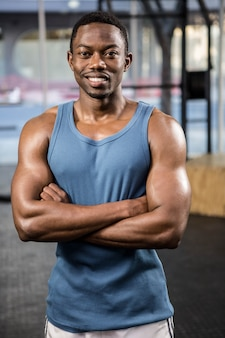 Der muskulöse mann, der mit den armen steht, kreuzte an der crossfit turnhalle