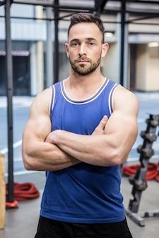 Der muskulöse mann, der mit den armen steht, kreuzte an der turnhalle