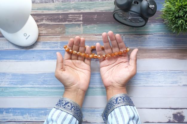 Der muslimische mann hält die hand in betenden gesten während der ramadan-nahaufnahme