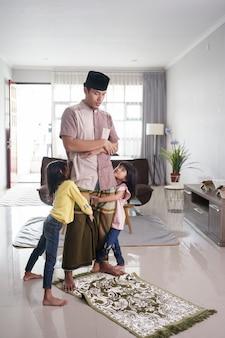 Der muslimische vater wird von seiner tochter gestört, während er zu hause betet
