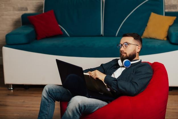 Der nachdenkliche junge mann ist zu hause vor dem laptop verlobt. student macht sich notizen in einem notizbuch. heimbildungskonzept.