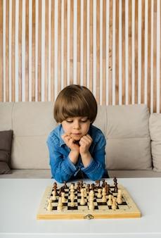 Der nachdenkliche kleine junge sitzt an einem tisch und spielt schach in einem raum
