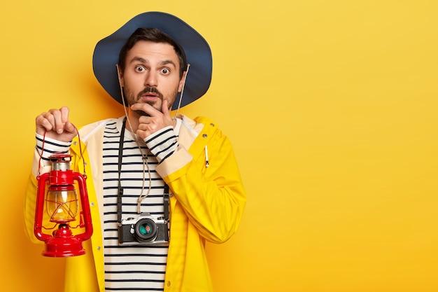 Der nachdenkliche männliche reisende hält das kinn, schaut direkt in die kamera, hält die gaslampe, trägt freizeitkleidung und benutzt die kamera zum fotografieren